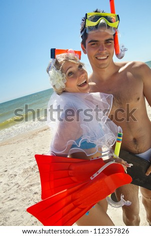 Romantic newly-married couple having fun on the beach, wearing mask and fins - stock photo