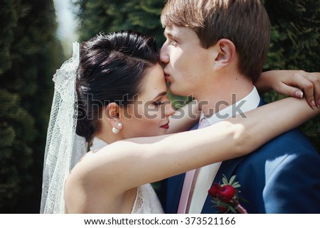 Romantic newlywed couple kissing and hugging in park closeup