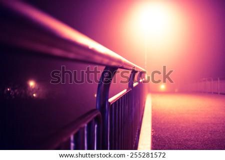 Romantic night city walk on a bridge in fog with street lights (toned). - stock photo