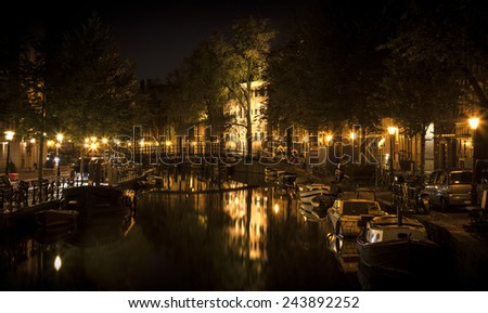 Romantic nocturnal view of Amsterdam: canal in the Red District. Buildings, bridge and boats are reflected in the water. The street lamps form a cross with the illuminated building in the center  - stock photo