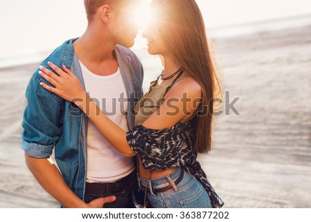Romantic outdoor fashion portrait of stunning couple in love hugs and posing on the beach at sunset, stylish clothes. Warm soft colors. Sunset. Horizon