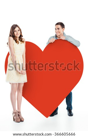 Romantic photo of beautiful couple on white background. Handsome young man and beautiful woman  standing near big red heart