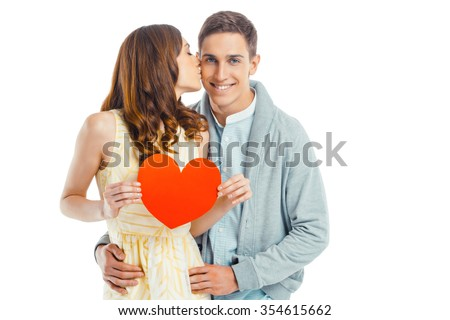 Romantic photo of beautiful couple on white background. Handsome young man smiling and looking at camera while his girlfriend holding Valentine card and kissing him - stock photo