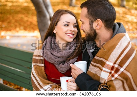 Romantic photo of cute couple outdoors in fall. Young man and woman sitting on bench with blanket and holding cups of coffee or tea - stock photo