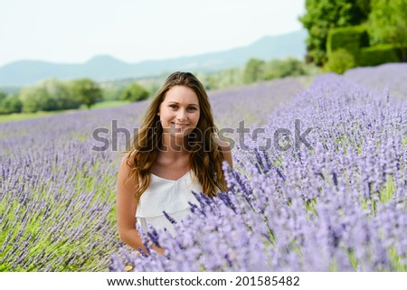 romantic portrait of a cheerful and attractive young woman enjoying summer and countryside in lavender field provence France - stock photo