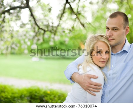 Romantic portrait of attractive young couple out doors in nature. - stock photo