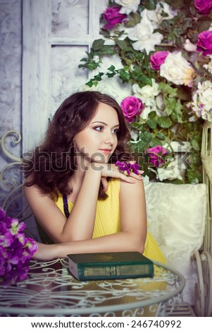 Romantic portrait of beautiful cheerful girl in room with flowers and book - stock photo
