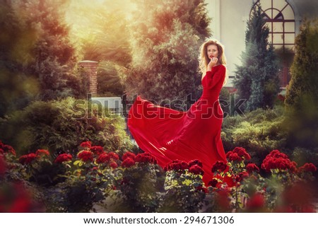 Romantic portrait of beautiful woman in fluttering red dress standing in the garden full of roses. Vintage photo. - stock photo