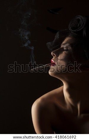 Romantic portrait of beautiful young woman with veil hat and cigarette