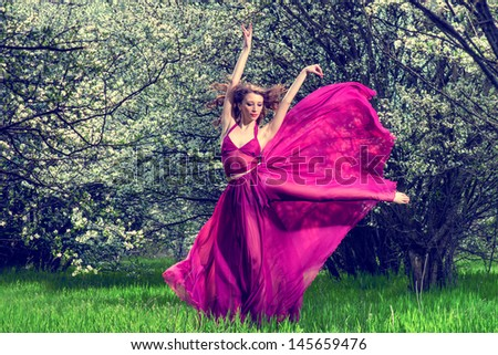 Romantic portrait of the woman in airy crimson dress dancing among the blossoming trees - stock photo