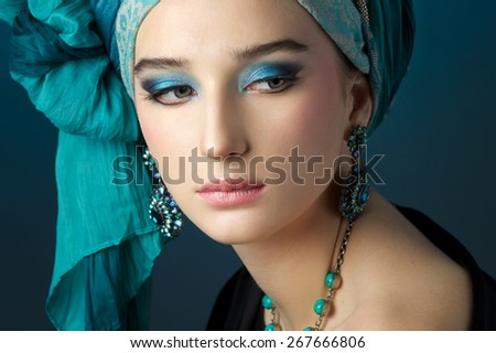 Romantic portrait of young woman in a turquoise turban with jewelry on a beautiful background