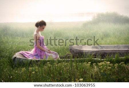 Romantic portrait of young woman in airy pink dress sitting in ruins at sunrise
