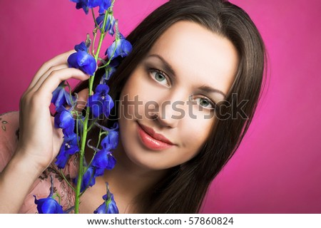 Romantic portrait of young woman with blue flower