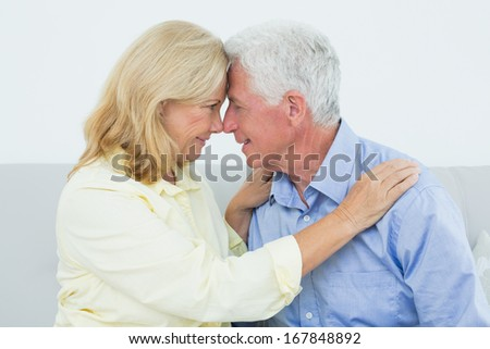 Romantic relaxed senior couple sitting on sofa in a house