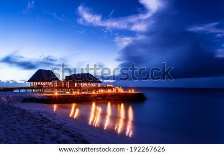 Romantic restaurant on the beach, beautiful night seascape, luxury resort on Maldives, dark blue sky, summer vacation concept - stock photo