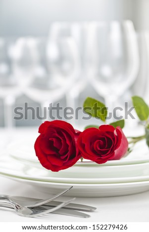 Romantic restaurant table setting for two with roses plates and cutlery - stock photo