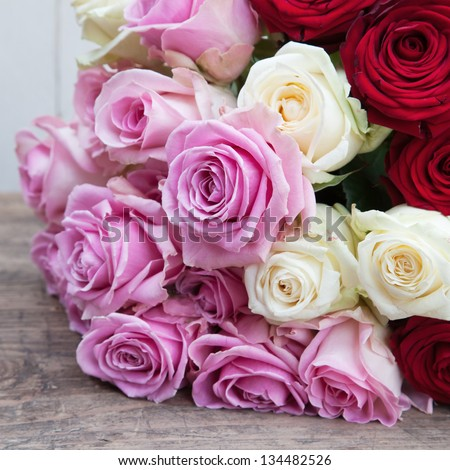 romantic rose bouquet lying on a wooden table - stock photo
