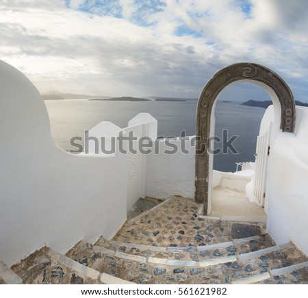 Romantic Santorini island in Greece: staircase through the arch leading to majestic view over caldera, panoramic image.