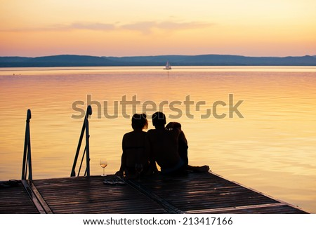 Romantic scene - Young couple sitting on a pier at a lake after sunset - stock photo