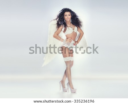 Romantic sensual brunette lady posing in white lingerie and big wings. Angel in heaven.  - stock photo