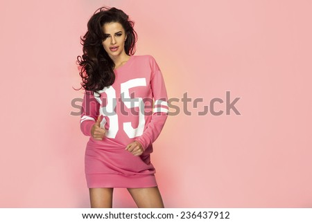 Romantic sensual brunette woman posing over pink background, smiling - stock photo