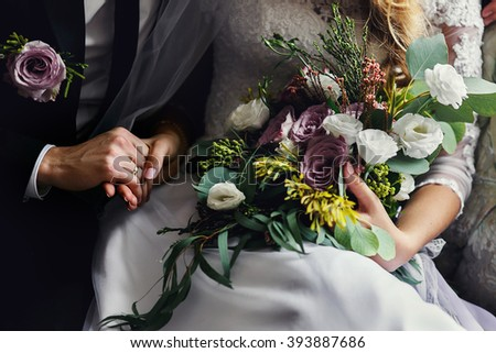 Romantic sensual newlyweds posing on luxury sofa with bouquet