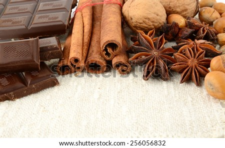 Romantic set of chocolate,anise,nuts and cinnamon on white fibre material like flax - stock photo