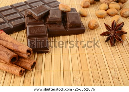 Romantic set of chocolate,anise,nuts and cinnamon on wooden mat - stock photo