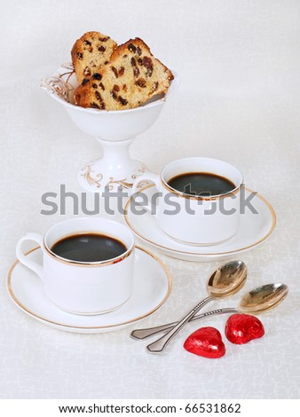 Romantic set: two cups of coffee with two heart shaped chocolate sweets