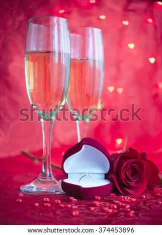 Romantic setup with two glasses of champagne, red rose and engagement ring on red background with bokeh in heart form. Marriage Proposal with diamond ring. Valentine's day background.  - stock photo