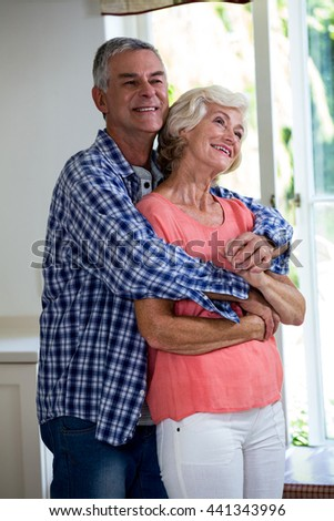 Romantic smiling couple embracing in kitchen at home - stock photo
