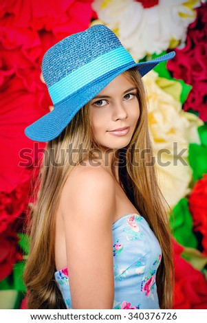 Romantic smiling girl posing in summer dress by a background of bright paper flowers. Beauty, fashion.