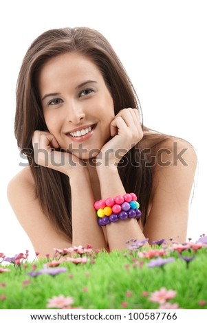 Romantic spring portrait of pretty girl with flower and grass, colorful bracelet, smiling at camera.