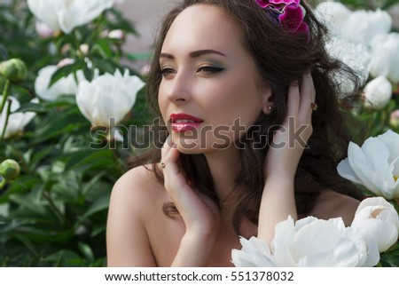 Romantic spring portrait of sensual young girl with peonies