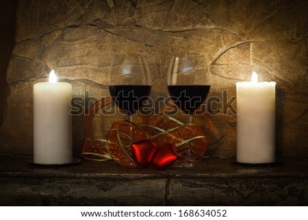 Romantic still-life. Two glasses of wine, candles and teddy red heart on stone wall background. Valentines day.