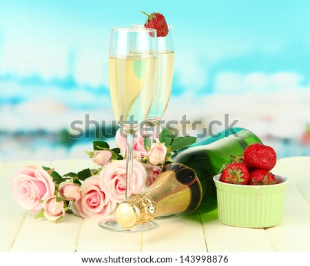 Romantic still life with champagne, strawberry and pink roses, on bright background