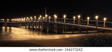Romantic summer night and illuminated pier  - stock photo