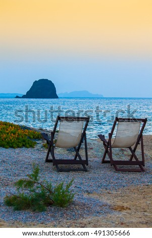 Romantic sunset in Greece.  - Empty chairs on the beach looking at the sea.