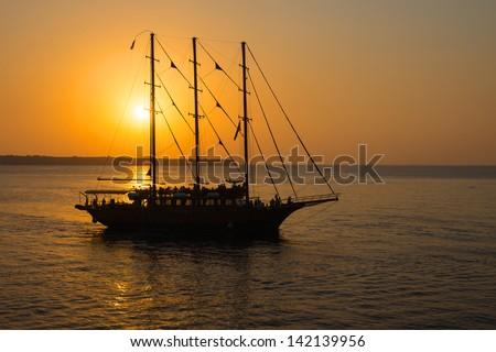 Romantic sunset with sailing ship - stock photo