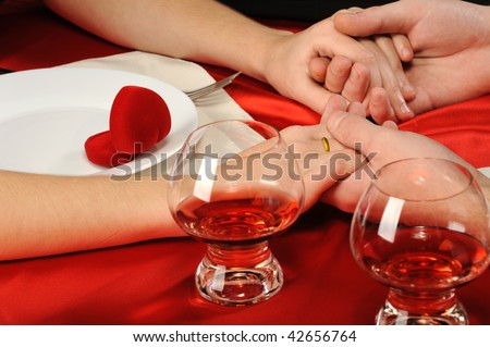 Romantic supper. A close up. Young the man does the offer to the girl. - stock photo