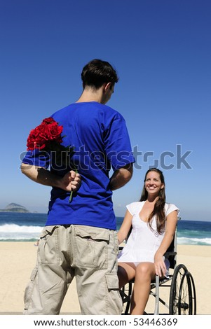 romantic surprise: man hiding red roses, a gift for his handicapped girlfriend - stock photo
