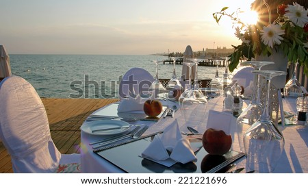 Romantic Table Setting on Pier at Sunset. Luxury wedding reception by the sea.  Wedding table with a beautiful sea view.  Wedding reception place ready for guests.  - stock photo