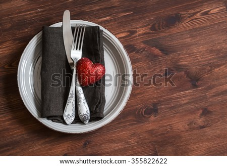 Romantic table setting - plate, knife, fork, napkin and a red heart, for Valentines day. On a dark wooden table. Vintage and rustic style - stock photo