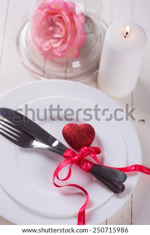 Romantic table setting. White plates, fresh rose in clochet, candle and little red heart.  Selective focus is on bow on ribbon. - stock photo