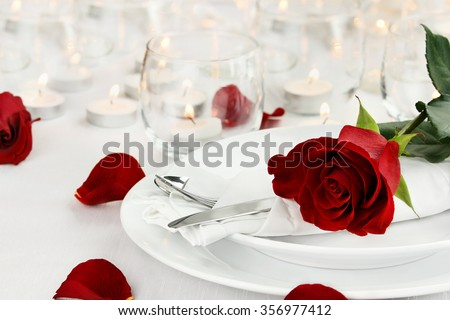 Romantic table setting with long stem red rose and candles burning in the background. Shallow depth of field with selective focus on rose. - stock photo