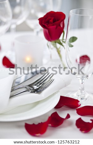 Romantic table setting with rose petals plates and cutlery - stock photo