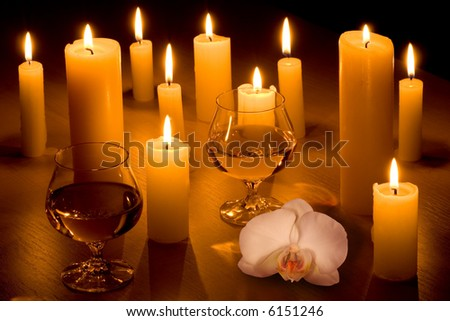 Romantic table with a lot of candles, two glasses of wine and white orchid. - stock photo