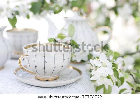 Romantic tea in the blossoming garden - stock photo