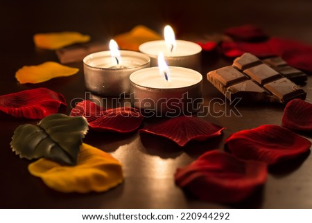 Romantic Tealights With Chocolate and Rose Petals - stock photo