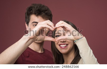Romantic teen couple composing an heart shape with hands and smiling - stock photo